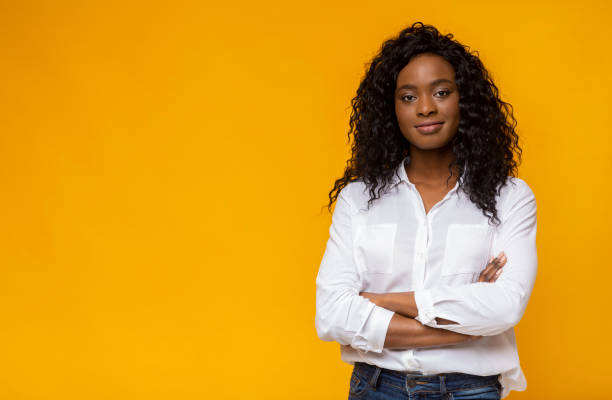 Confident young african woman posing on yellow studio background stock photo
