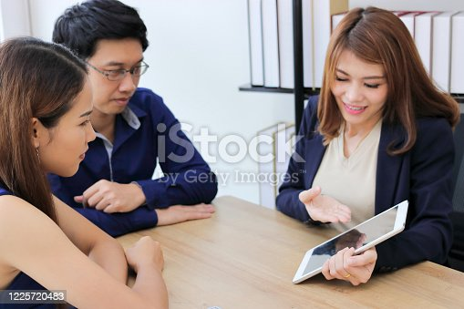 1129638619 istock photo Confident young Asian investment advisor business woman discussing to her client. 1225720483