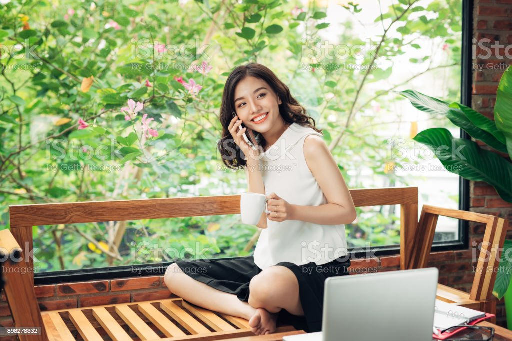 Confident young asian woman in smart casual wear listening to smartphone stock photo