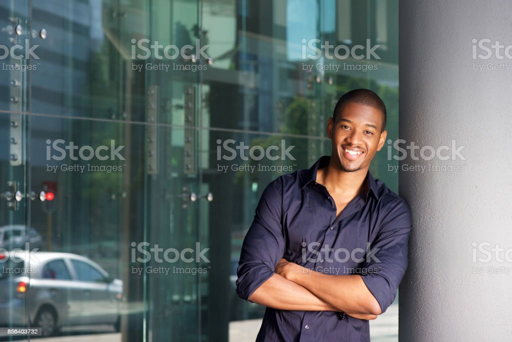 confident young black man smiling with arms crossed stock photo