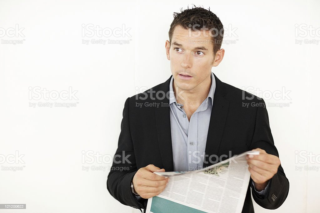 Confident young business man looking away with newspaper royalty-free stock photo