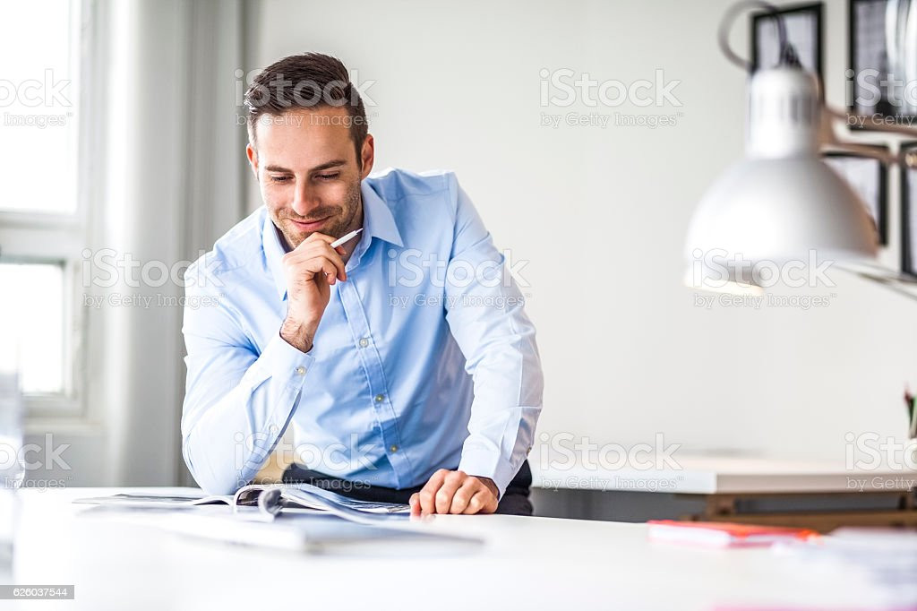 Confident young businessman analyzing brochure at desk in office – Foto