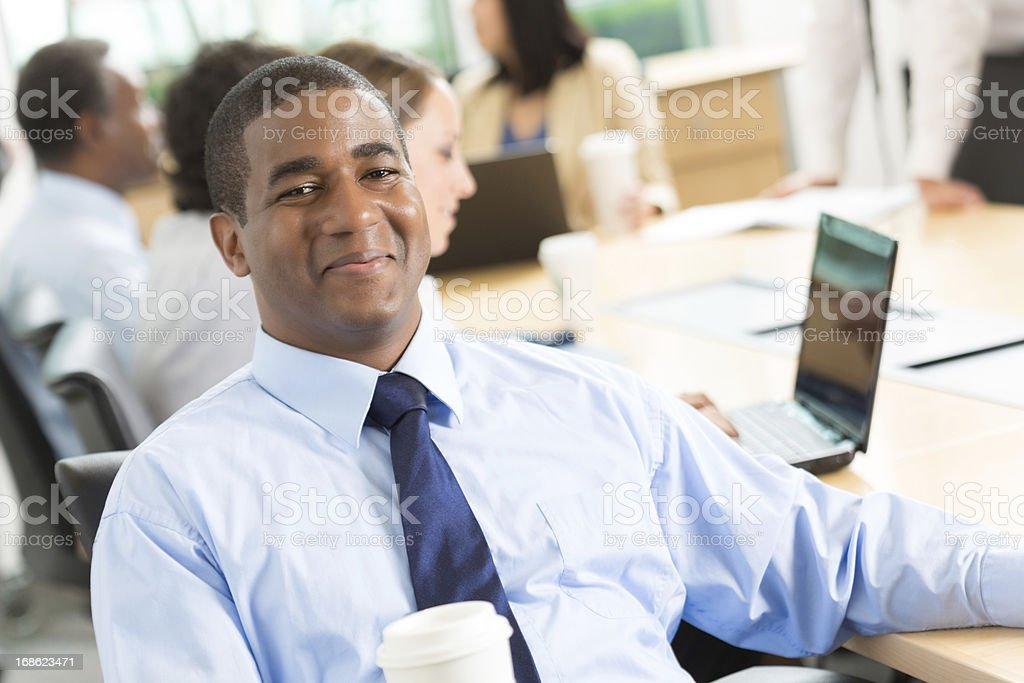 Confident young businessman in conference room with his peers royalty-free stock photo