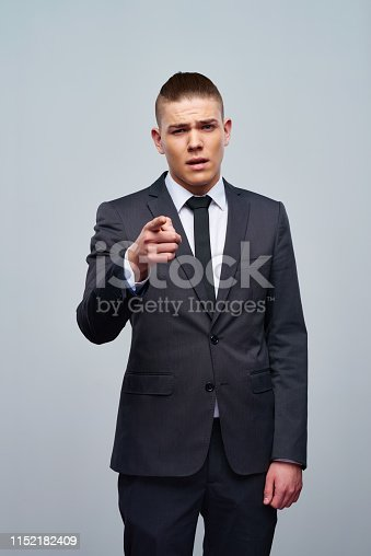 Handsome young man in trendy suit pointing at camera looking confidently on gray background
