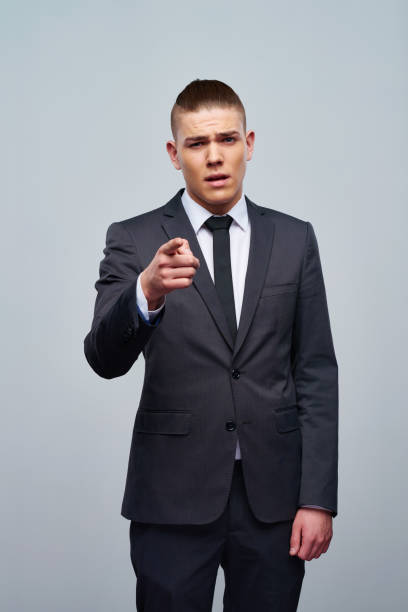 Confident young businessman pointing at camera stock photo