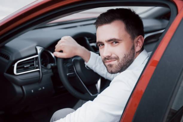Zuversichtlich junger Geschäftsmann sitzt am Steuer seines neuen Autos – Foto