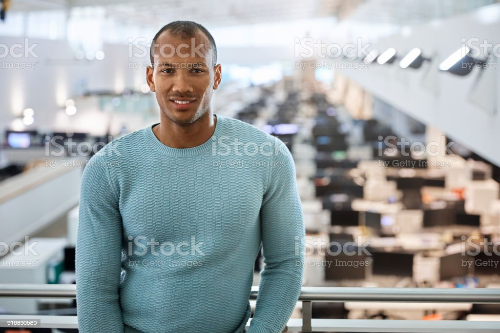 Confident young businessman standing at railing stock photo
