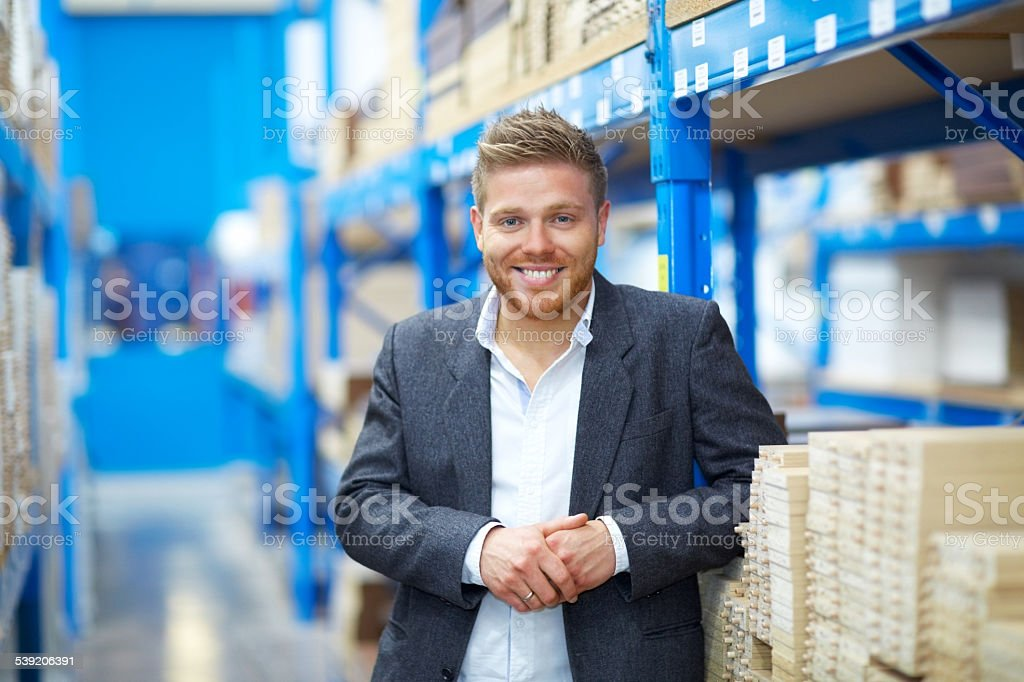 Confident young businessman standing in warehouse stock photo
