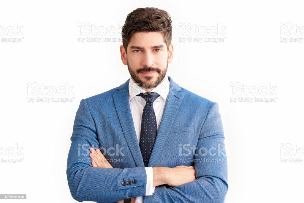 Jeune homme d'affaires confiant vêtu de costume en se tenant debout au fond isolé - Photo