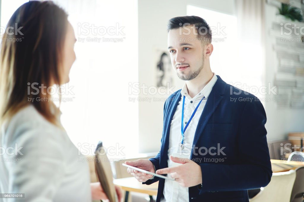 Confident young businessman with tablet computer in his hands and accreditation badge around his neck talking with unrecognizable female colleague at business event royalty-free stock photo
