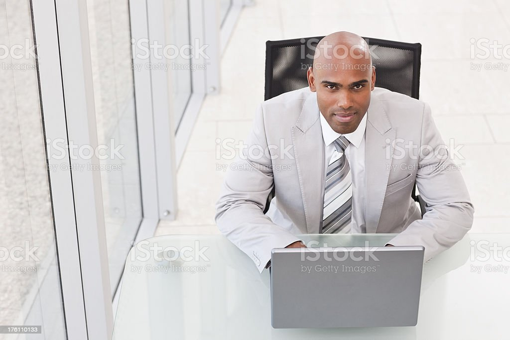 Confident young businessman working on a laptop royalty-free stock photo