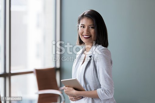 1150572102istockphoto Confident young businesswoman in her office 1138904465