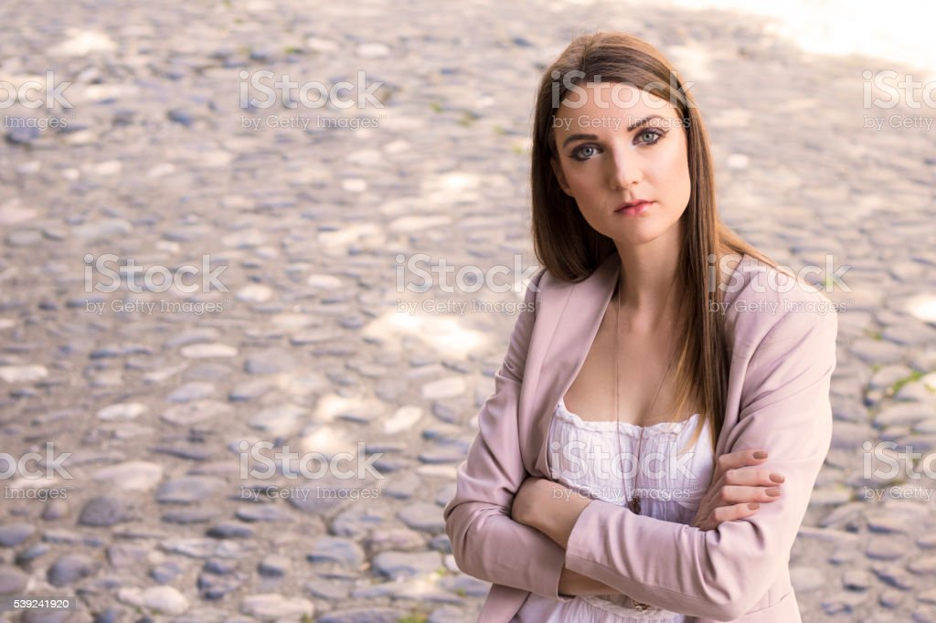 Confident young businesswoman keeping arms crossed and looking a royalty-free stock photo