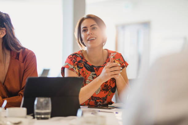 Confident young businesswoman listening carefully at conference table stock photo