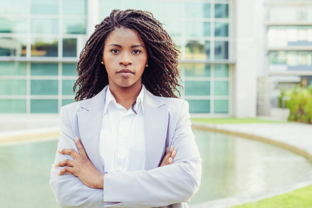 Confident young businesswoman looking at camera stock photo