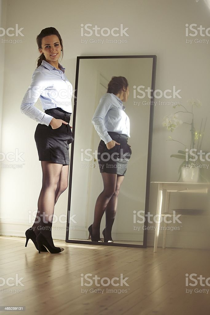 Confident young businesswoman posing in front of mirror stock photo