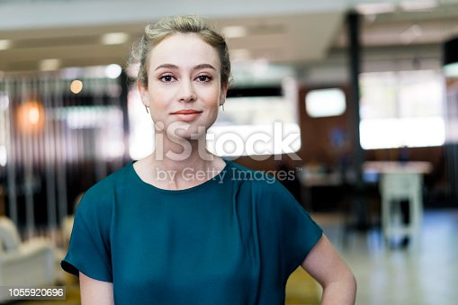 Portrait of beautiful businesswoman standing at creative office. Confident female professional is at workplace. She is in green casual.