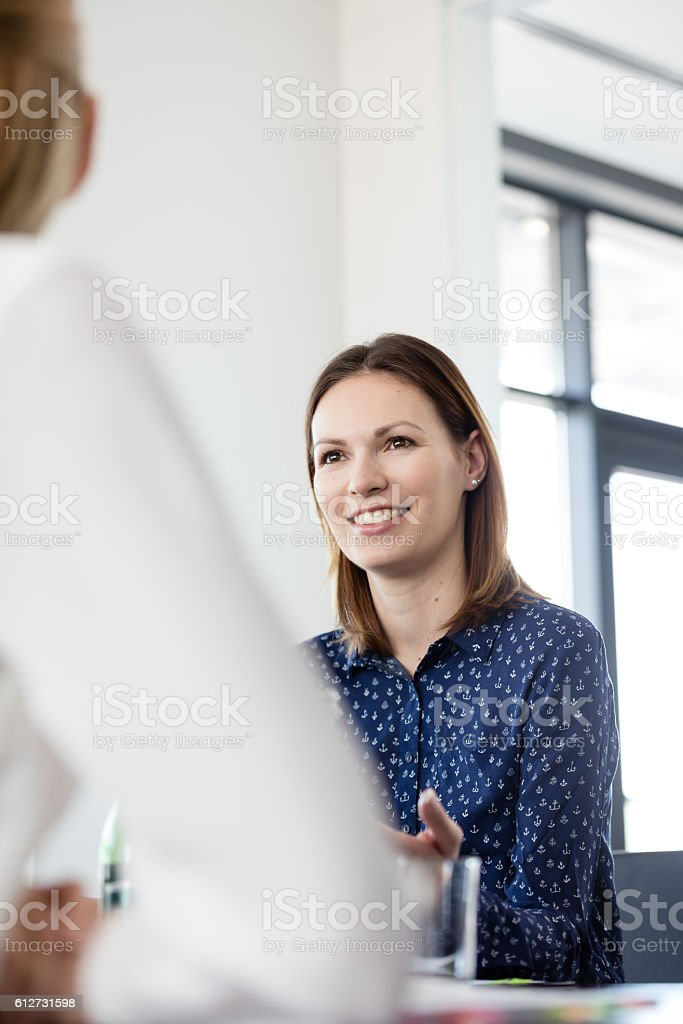 Confident young businesswoman talking with female colleague in meeting room royalty-free stock photo