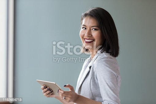 1150572102istockphoto Confident young businesswoman with digital tablet 1152654713