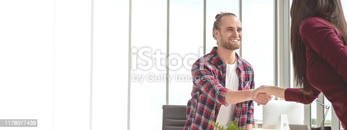 istock Confident young caucasian asian man shaking hands with partner woman in business agreement smiling together feeling happy. Banner of young business couple in deal, partnership and handshake concept. 1178077439