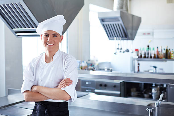Confident young cook Young cook standing cross-armed in restaurant kitchen chef's whites stock pictures, royalty-free photos & images