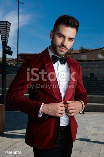 confident young elegant man wearing red velvet tuxedo, arranging coat, outdoor in an urban scene