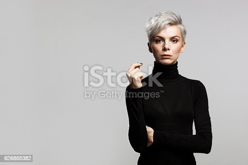 Portrait og young woman with short gray hair wearing a black turtleneck sweater. Looking confident.