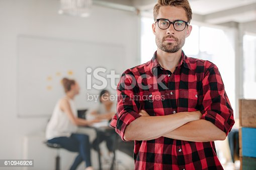 624700110istockphoto Confident young entrepreneur standing in office 610946926