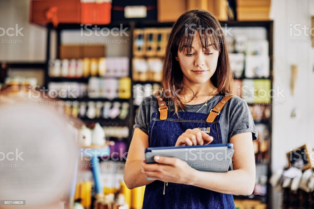 Confident young entrepreneur using digital tablet in delicatessen stock photo