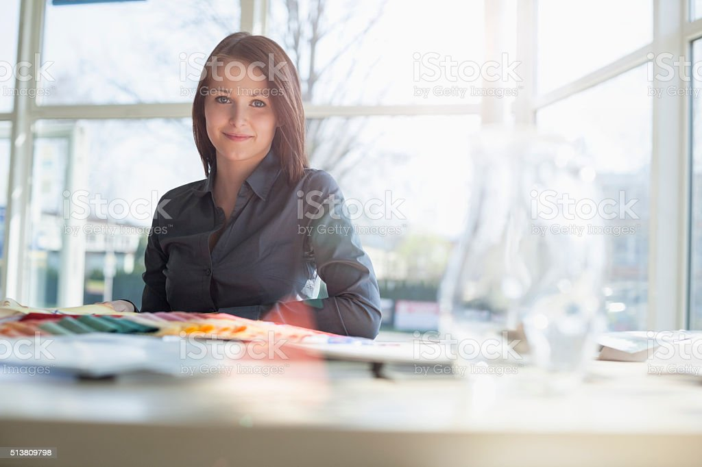Confident young fashion designer sitting at desk in office stock photo