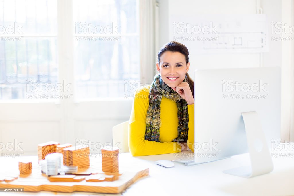 Confident young female architect at her desk stock photo