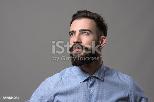 istock Confident young handsome stylish business man looking up at copyspace 886534034