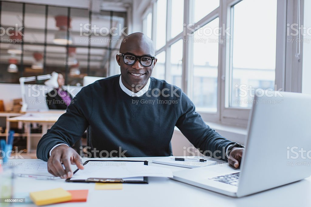 Confident young man at his desk stock photo