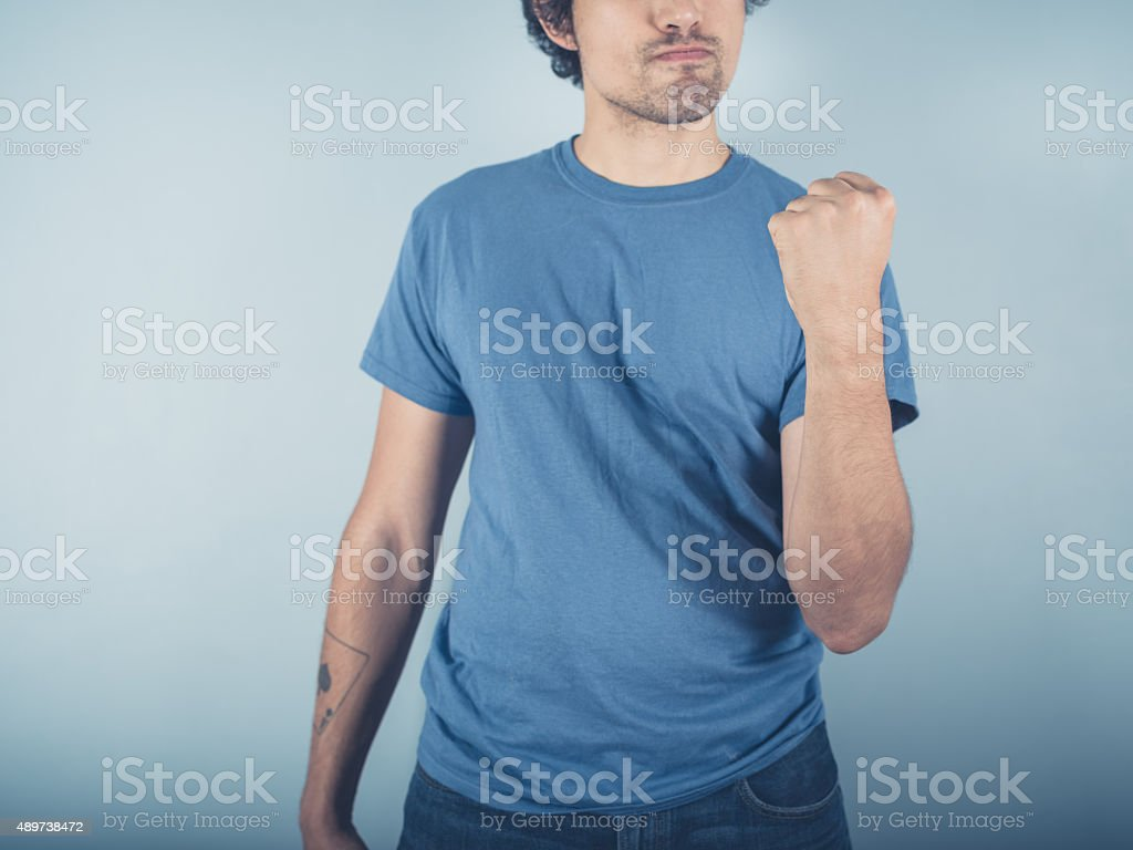 Confident young man fist pumping stock photo