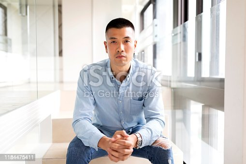Portrait of a young Asian man posing in front of the camera.