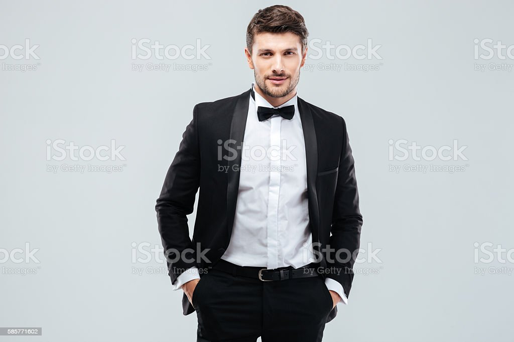Confident young man in tuxedo with bowtie stock photo