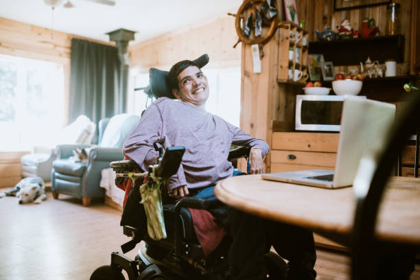 Confident Young Man In Wheelchair At Home stock photo