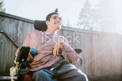 A cheerful young adult man with cerebral palsy smiles outdoors, holding a small dumbbell weight.