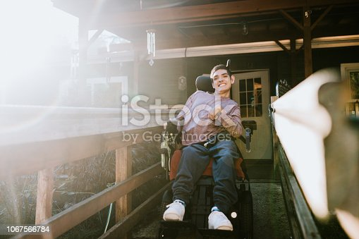 A cheerful young adult man with cerebral palsy drives down a wheelchair ramp to go outdoors on a bright sunny day.