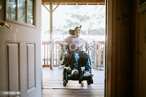 A cheerful young adult man with cerebral palsy drives up a wheelchair ramp to enter his home.  Horizontal image with copy space.