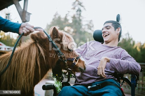 A cheerful young adult man with cerebral palsy spends time with a pony, used as a therapy animal.