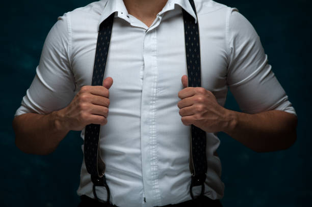 Confident young man posing on dark background Closeup of young man wearing formal suit posing on blue background suspenders stock pictures, royalty-free photos & images
