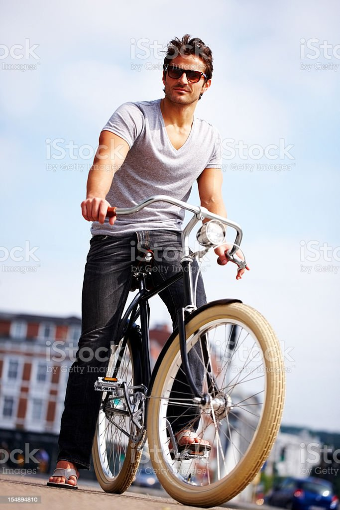 Confident young man posing with his bicycle royalty-free stock photo