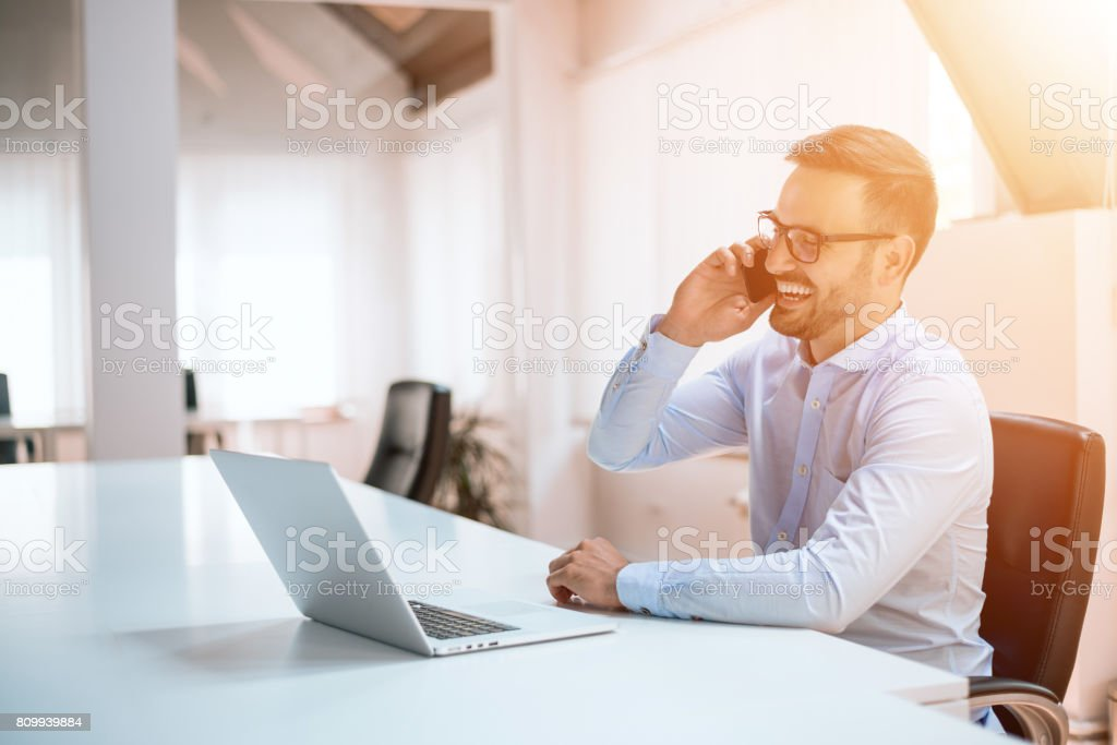 Zuversichtlich junger Mann am Telefon im Büro – Foto