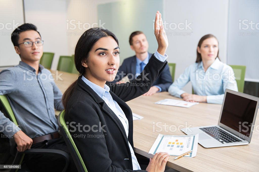 Confident young manager raising hand at workshop Confident young Latin-American female manager sitting at wjrkshop with multiethnic business people and raising hand to ask question Adult Stock Photo