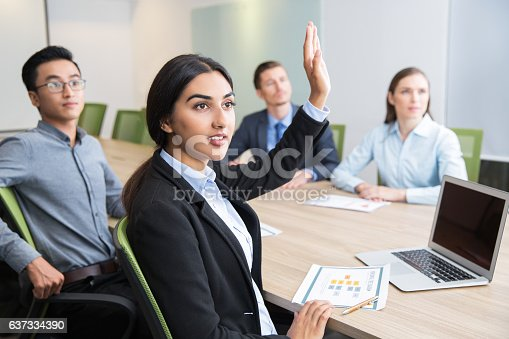 istock Confident young manager raising hand at workshop 637334390