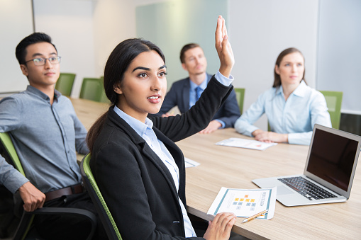 Confident Young Manager Raising Hand At Workshop Stock Photo - Download Image Now