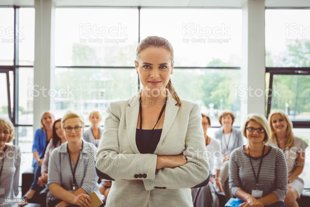 Confident young speaker in seminar hall Portrait of confident young female speaker with audience  sitting in background Adult Stock Photo