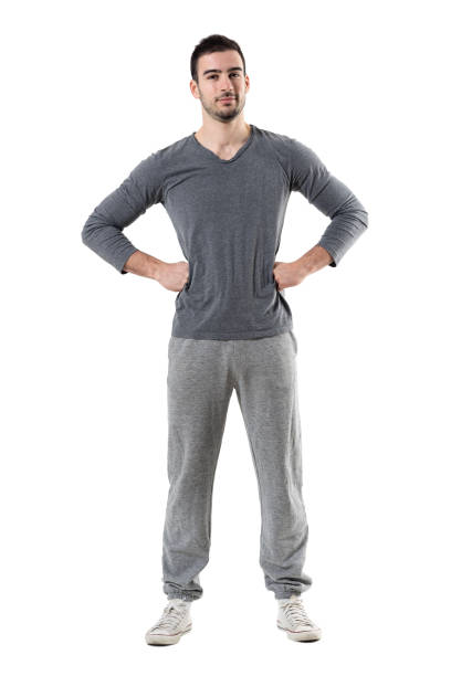 confident young sporty athlete with hands on hips looking at camera - sweatpants stock-fotos und bilder