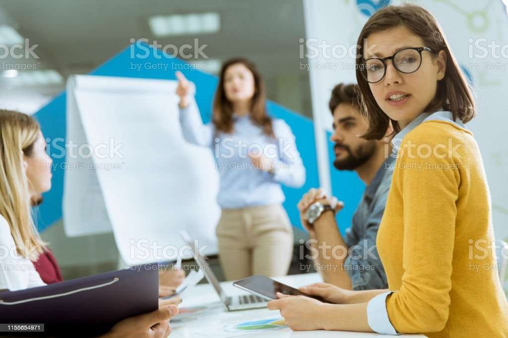 Confident young team leader giving a presentation to a group of young...
